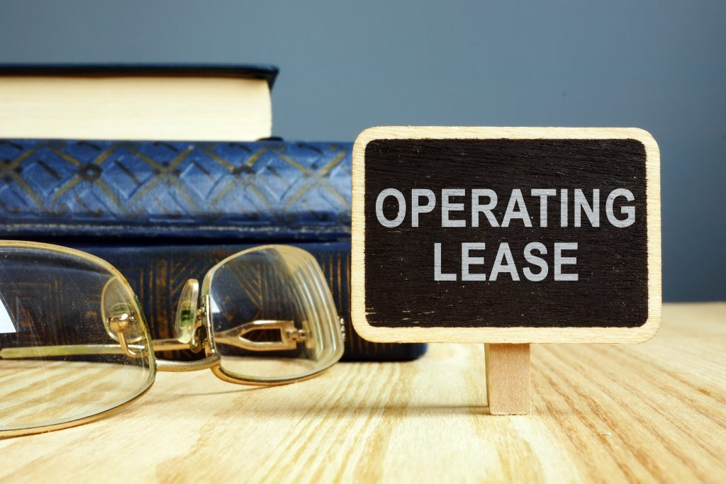 Stacked books, glasses and a small operating lease sign